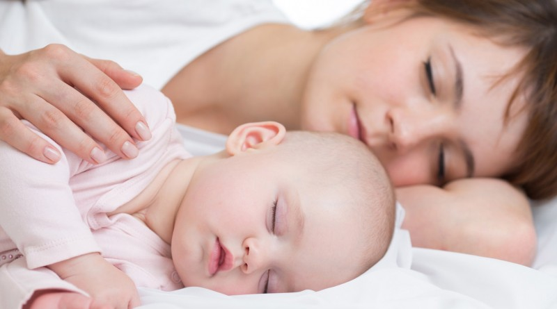 Young mother and her baby sleeping together