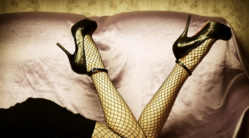 Sexy female legs in high heel black shoes and fishnet stockings. Retro style