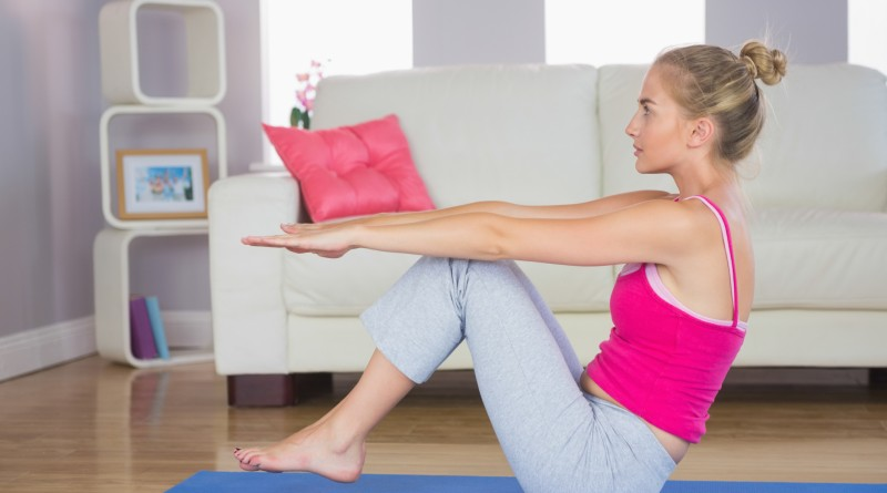 Sporty focused blonde doing core exercise